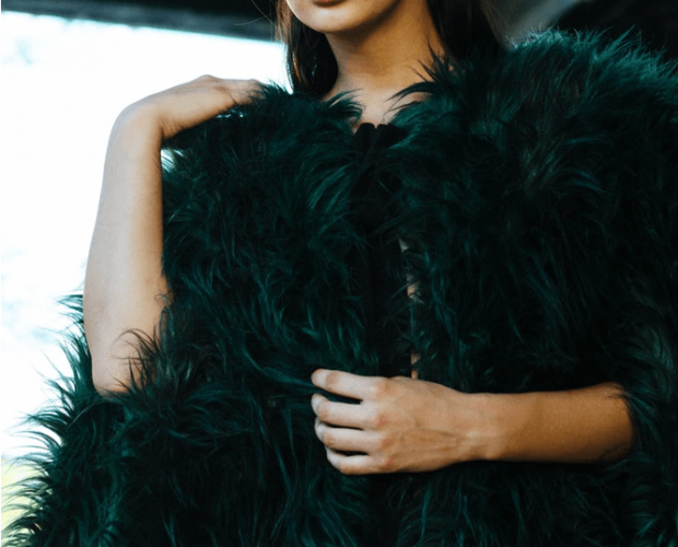 Woman wearing a black fur coat with a dress for cold weather