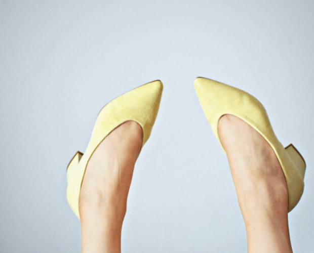 Yellow shoes on feet in the air