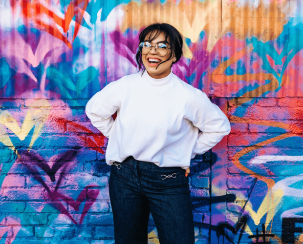 Woman standing near wall full of colors in white sweatshirt and glasses