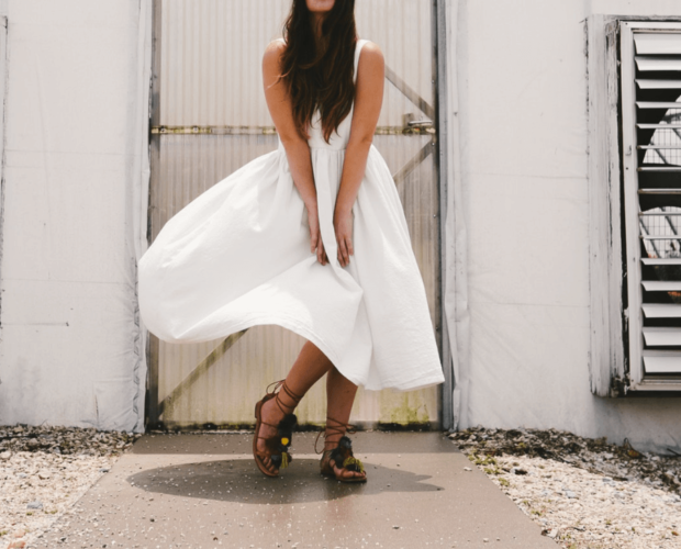 Woman wearing a white dress malfunction which is being lifted by the wind as she tried to hold it down with her hands