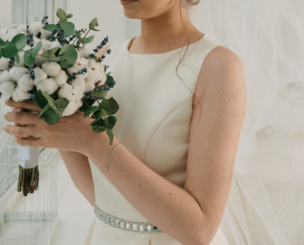 Woman wearing white sheath bridesmaid dress and holding a bouquet of flowers