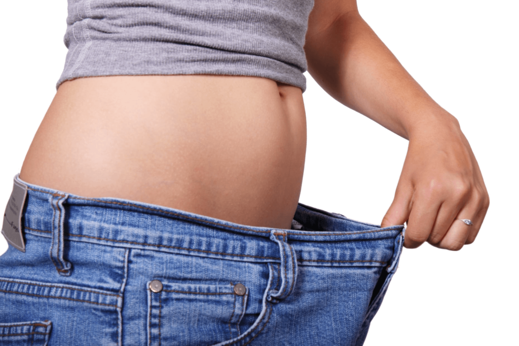 Woman who has lost weight stretching the waist of her jeans to see how much she has lost