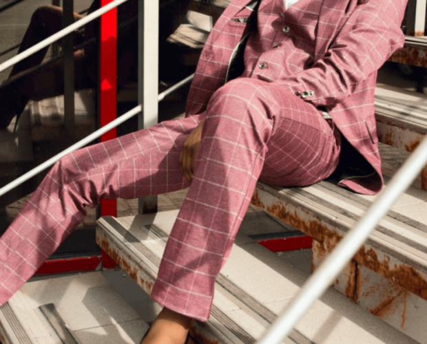 Woman wearing pink suit and sitting on stairs