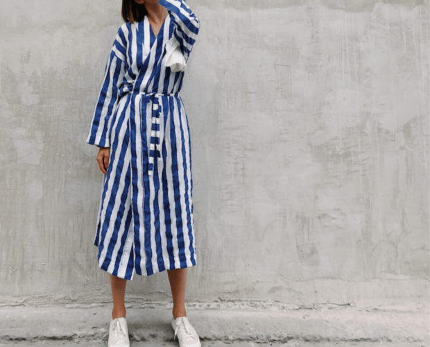 Woman wearing modest fashion stripy dress and standing by wall