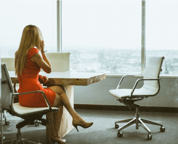 Woman sitting at her office desk at work and wearing a red dress and heels