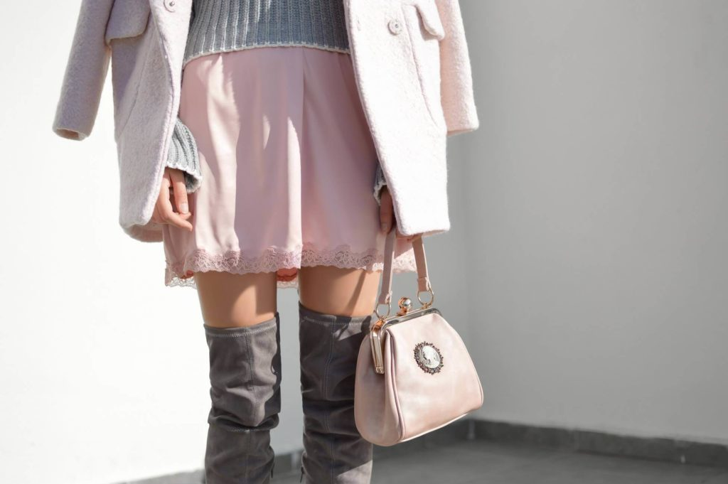 woman wearing pink dress jacket and bag with over knee boots